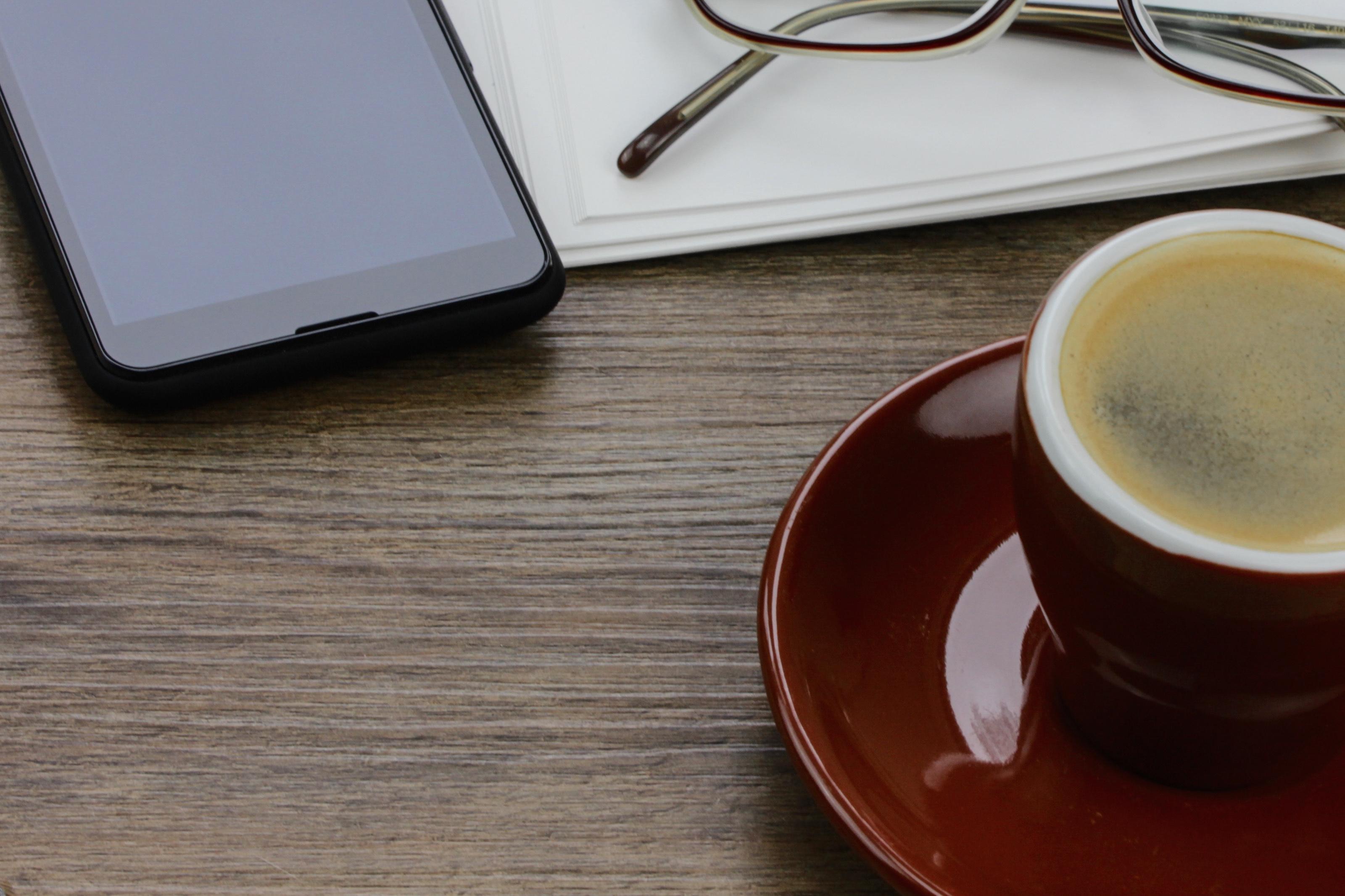 phone, glasses, notebook, espresso