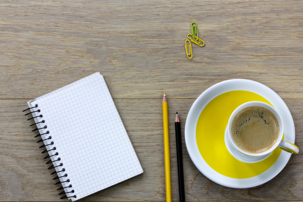 desk, office, coffee, paper clips, pencils, notebook, yellow cup