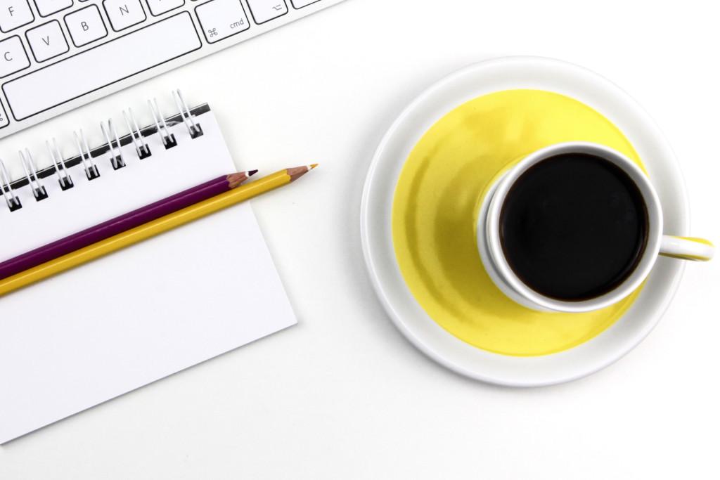 desk, notebook, pencils, coffee, yellow cup, keyboard